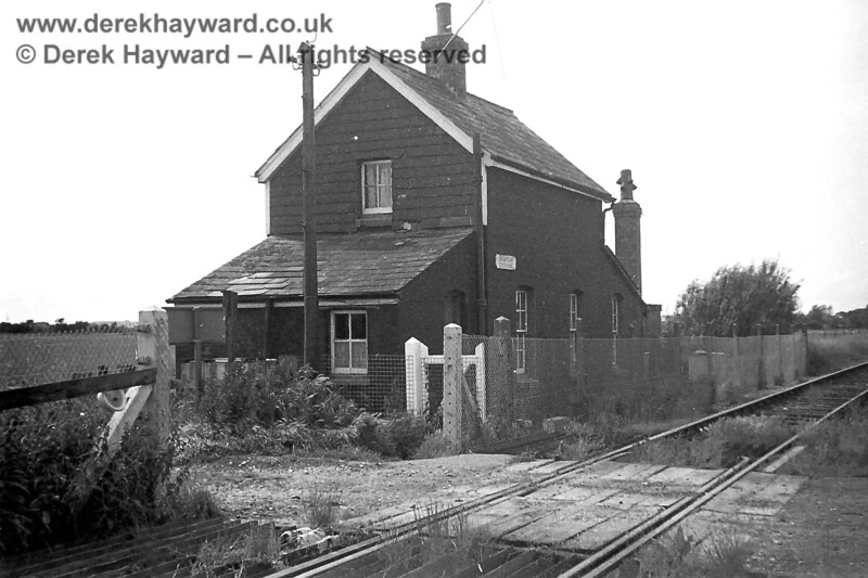 """Mountain Crossing in 1969 looking south towards Lydd.  Copyright Neil Smith. Mountain Crossing is located on the crossroads between Narrowbush Lane, Eighteen Acre Lane, Washington Lane and Mountain Lane.  The pictures of the house and it's surroundings date from 1969 (or possibly 1970), by which time the crossing gates had been removed and """"Crossing Keeper"""" duties were no longer required.<br /> <br /> The owner of the images, Neil Smith, reports that Mountain Lane and Eighteen Acre Lane were green lanes and therefore mainly used for farm vehicles and massive flocks of sheep which sometimes stretched the length of Mountain Lane to Narrow Bush Lane with """"Marsh Lookers"""" with sheep dogs at the front and rear.  They were very happy to accept a cuppa with his Mother at the crossing on their way over the railway.<br /> <br /> The house had no running water or flushing lavatory. Instead there was an """"Elsan"""", which was emptied into a freshly dug earth pit when required.<br /> <br /> Rain water was collected in tanks at both ends of the house with a small tank for drinking water which was delivered from an engine tender. In the scullery there was a copper for heating hot water with a fire for doing the weekly wash and a tin bath for baths in front of the fire. When not in use there were buckets for Rain Water and Drinking Water placed on top of the copper.<br /> <br /> Lighting was Tilly lights or Oil lamps until 1961 when Dad (Mr Smith) bought a diesel generator which produced 1250 watts; just enough for the few lights he had installed and a black and white television.  The old style (405 lines) aerial can be seen in some of the pictures.  <br /> <br /> For heating coal was thrown from the steam trains as they passed at their normal speed, so the fuel ended up strewn along the line.  It was then collected from along the track by wheel barrow. <br /> <br /> One of the images, taken from a bedroom window, shows a field which went with crossing.  The remains of a railway carria"""