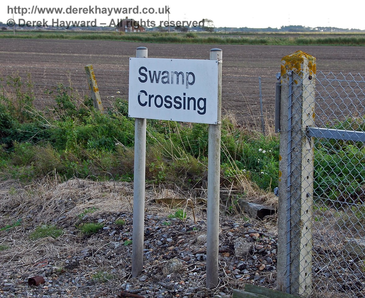 Swamp Crossing has a sign of standard construction.  It is not a particularly attractive name, but it is, no doubt, traditional. The area to the west is Walland Marsh. 08.10.2008