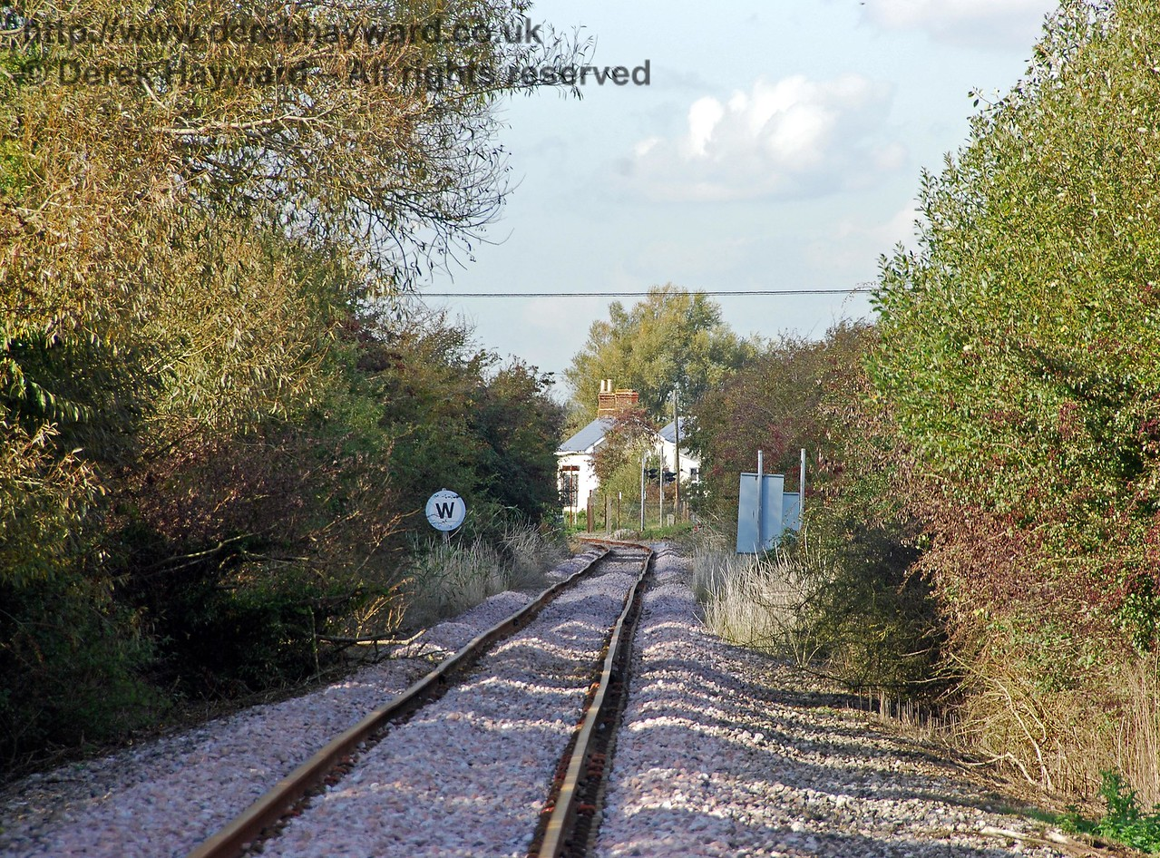 Continuing south from the former station at Brookland Halt, it is only a short distance to Boarmans Crossing.  This shot looks back north towards the Brookland level crossing and the former station building can be seen in the distance. A whistle sign is needed as part of the protection for the crossing. The train is required to stop before continuing north over the A259 at Brookland level crossing. 08.10.2008