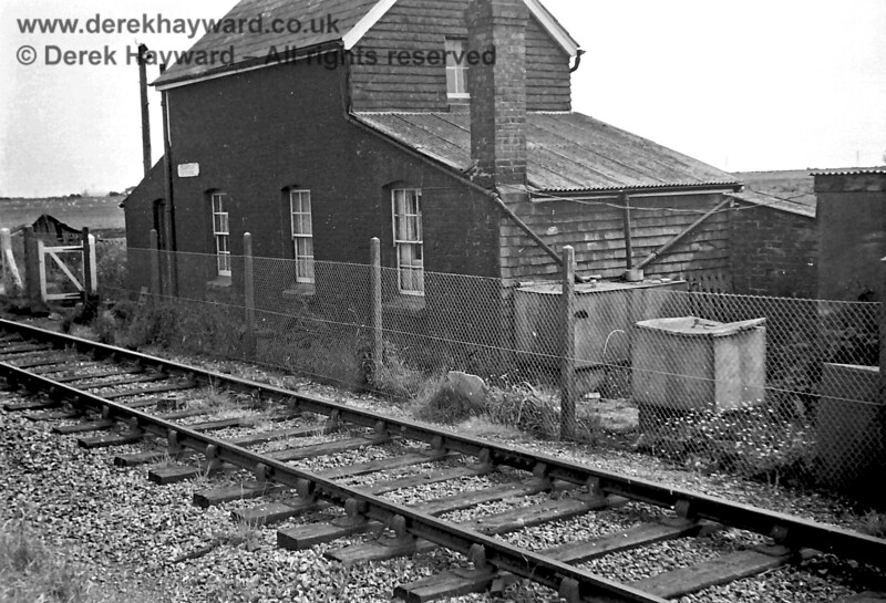 """Mountain Crossing in  1969.    A large tank on the end of the house collected rainwater from the roof (pipes from the gutters lead into it).  The smaller tank nearer the camera was for the deliveries of drinking water which came from an engine tender.  A  plate saying """"Mountain Crossing"""" is on the side of the house facing the railway.  The names were needed because of the large number of crossings on the line.  Copyright Neil Smith."""