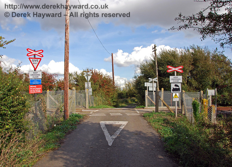 Fielders Crossing looking east. This lane is also (absolutely) unsuitable for motor vehicles beyond the crossing but the local authority sign is further back down the lane and out of shot. There is an unusual Beware of Trains sign on the right which is certainly not of current design, but it would be hard to miss the crossing.  The track beyond the crossing gives access to Coldharbour Farm. 08.10.2008