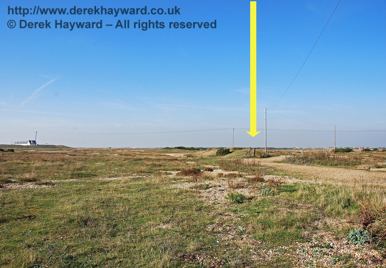 Moving to the old Dungeness Station and looking north, it is now hard to distinguish the station site in the bleak landscape. The arrow indicates the hump in the shingle which marks the position of the old platform. The station closed to passengers in 1937. 27.09.2008