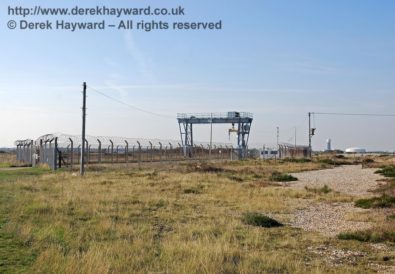 A second view of the secure sidings looking west. The original Dungeness branch ran through what is now the secure site, out of the gates on the left, and followed what is now the approach road to the power station. It is assumed that the railway embankment across the marsh was needed as a firm base for the power station road. On the right of the picture the area of shingle marks the approximate position where the second branch to Lydd-on-Sea and New Romney curved away east.  There was no obvious way to photograph the site of the old junction, and a preliminary inspection of the remainder of the New Romney branch revealed few surviving features. The trackbed does, however, still show up clearly on Google Earth.  At ground level it is less obvious. 27.09.2008