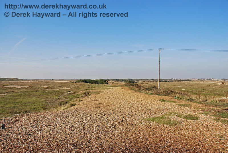 Looking north from the old platform at Dungeness Station the slightly raised embankment shows the route of the old track. The main branch line ran almost straight, heading through what is now the clump of bushes. The deviation in the shingle path is explained by three sidings that turned right to serve a ballast pit.  These are clearly shown on a 1907 map. 27.09.2008