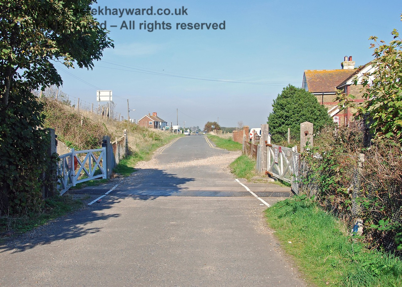 Lydd Town level crossing, looking east.  The former Station Master's house is just beyond the crossing. 27.09.2008