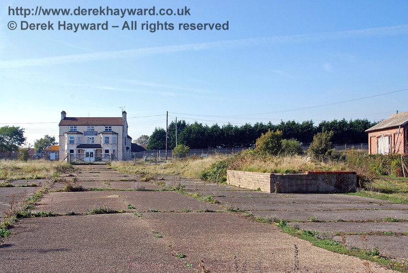 A general view of Lydd Town goods yard looking north.  At some stage the majority of the goods yard was surfaced with concrete slabs. There were extensive goods facilities at the station including four sidings and a branch to the Lydd Army camps which were established to the south and west of the town.  There is no obvious trace of this branch which curved away to the left of the picture. The army camps generated substantial goods and passenger traffic, especially during both World Wars. 27.09.2008