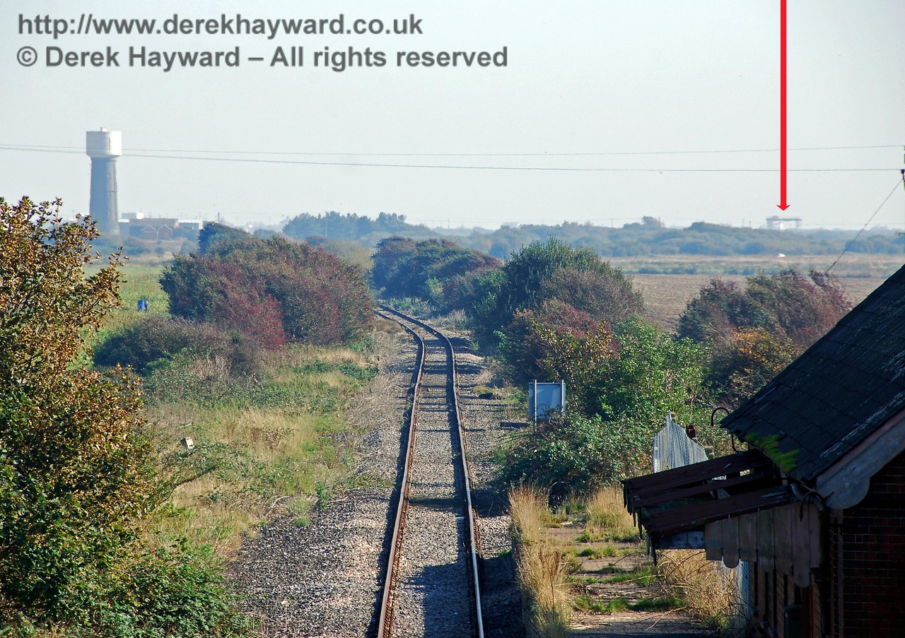 The same view south from the overbridge at Lydd Town Station but with a long lens. The line curves left past the water tower and then sweeps right in an arc to terminate at the compound where the overhead crane can just been seen in the haze (arrowed). There are a number of features in this section (not currently photographed and listed north to south): the site of Bakers Accommodation Crossing (closed and removed); an unnamed Public Footpath Crossing; Bridge 1854 (over a drainage ditch); Blacklocks Accommodation Crossing; the original junction and alignment of the railway to New Romney (closed and lifted); the site of Stanfords Accommodation Crossing (closed and removed); the site of a siding for gravel extraction (lifted but possibly to be reinstated); the site of a private siding for the waterworks (closed and lifted); Folkestone Waterworks Accommodation Crossing and Public Footpath Crossing; and the site of an unnamed foot crossing made redundant by the flooded gravel workings.  27.09.2008  The power station sidings are in a separate gallery.
