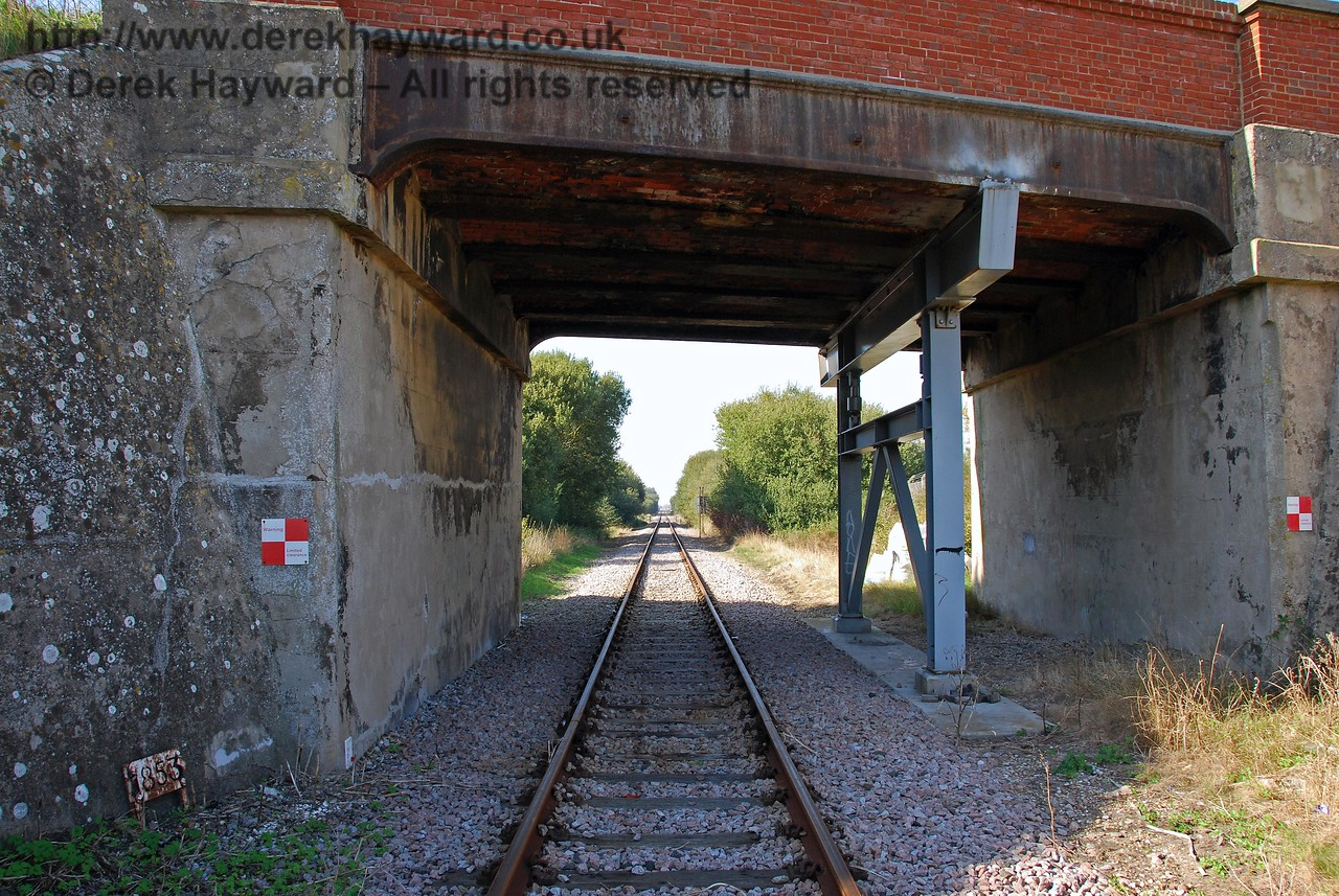 This shot looks north from Lydd Town level crossing, through the overbridge. Old maps suggest that there was only ever a single track under the bridge, but it appears to have been built to cater for double track. It is assumed that the additional support is a later addition. 27.09.2008