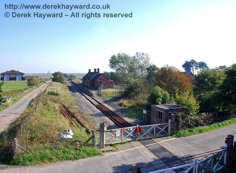 A general view of Lydd Town Station and level crossing looking south from the overbridge. The goods yard is on the right behind the trees (the roof of the goods shed can just be seen). 27.09.2008