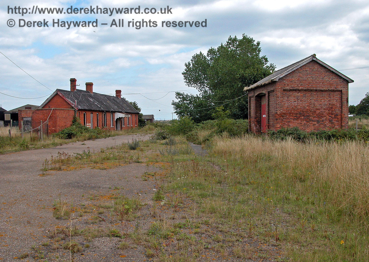 This view of Station Approach, looking south and taken on 08.08.2005, shows the station entrance and the old goods shed. Lydd Town Station had a large goods yard and the siding serving the goods shed entered from the far end of the station and ran to the left of the goods shed, with goods being unloaded through the red door. The siding contnued past the shed and terminated to the bottom right of the photo, following the line of the high grass.