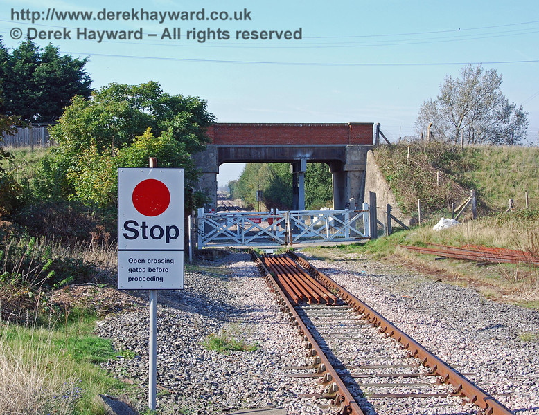 Turning round, this is the view north from the northern end of Lydd Town Station platform. The new sign in the foreground gives a rather obvious instruction. One hopes that the driver could have worked out what to do...! (There is no sign telling him to stop beyond the crossing and shut the gates, but it can only be a matter of time before someone puts one up....) 27.09.2008