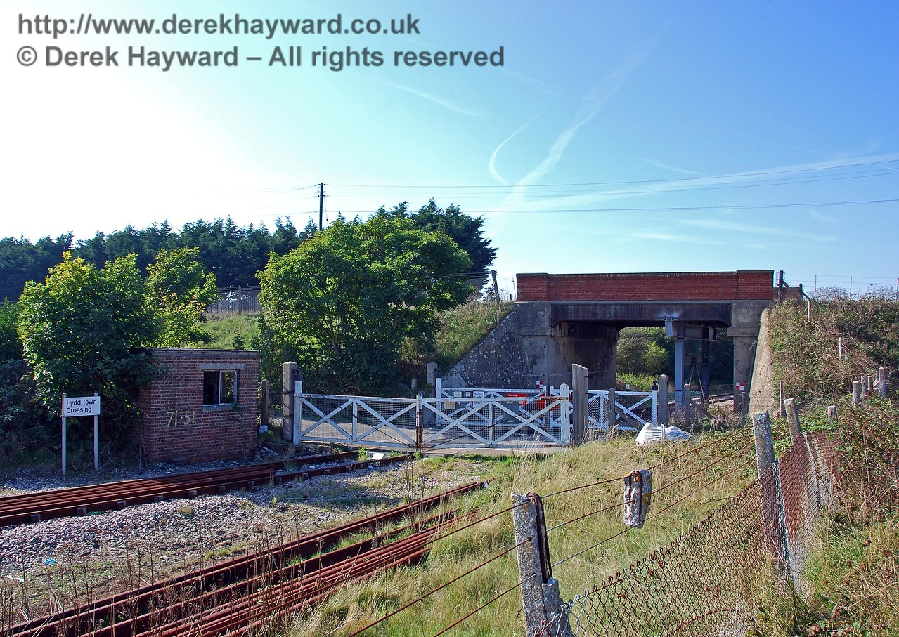 This view, looking north, shows Lydd Town level crossing, which was provided in 1961 for heavy vehicles en route to the power station.  This is known as a Trainman Operated Crossing (TMO). Beyond is the line's only overbridge (Bridge 1853), which currently carries the main road. Other sources state that the small brick building contains a ground frame, but I am unable to say whether this is true.  It clearly had some function relating to the crossing, but now seems in a poor state of repair, with broken windows. 27.09.2008