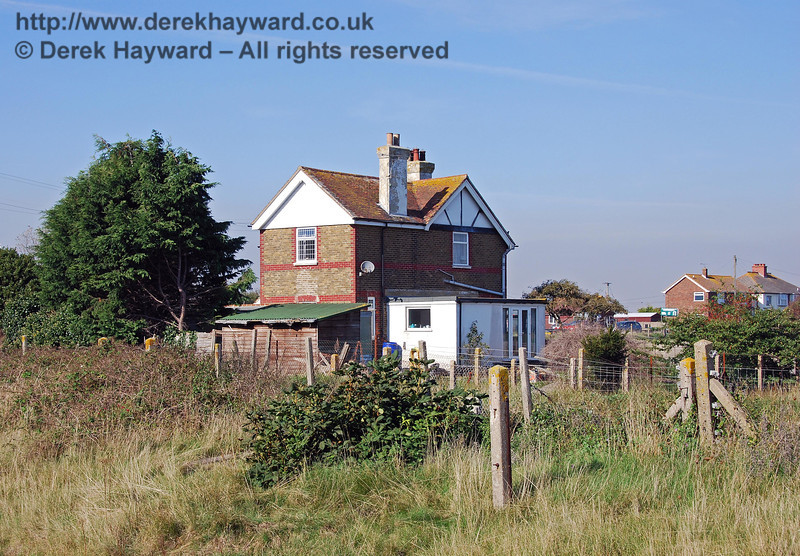 Looking east from the platform, across the line, this is the old Station Master's house at Lydd Town Station. A path led directly from the house across the track to the station, it's position being marked by the disused fence post in the foreground. The path passed to the left of the post and through a gate in the fence behind the bush. 27.09.2008