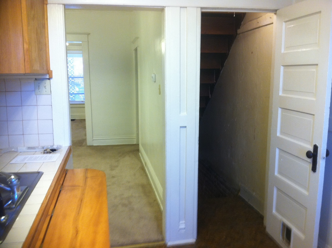view from the kitchen toward the main body and door to basement