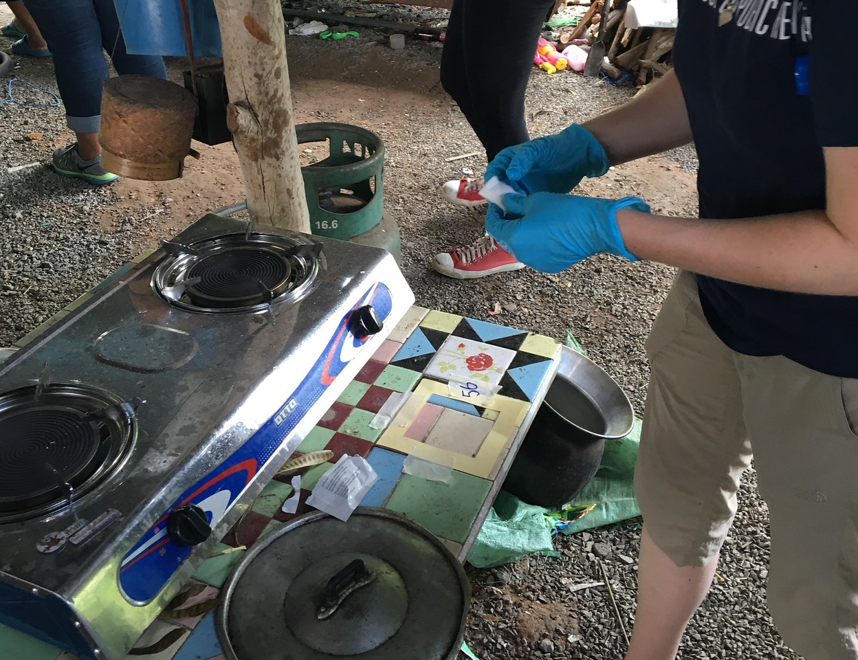 A UM graduate student performs a wipe sample for metal dust on a food preparation surface located adjacent to electronic waste recycling work areas.