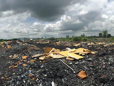 General waste landfill and electronic waste burn site in Kalasin, Thailand. The site is immediately adjacent to a large rice paddy.