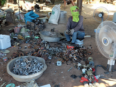 Electronic waste worker dismantling and extracting copper from oscillating fan motors behind his home; worker is wearing fabric gloves, long sleeves, pants, and a ski mask as protective equipment.