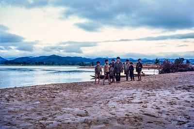 Boys on flooded Dak Bla river bank
