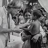 John examining sick child with Francoise
