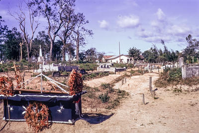Fresh graves (Ben Het chopper crash) across from seminary. International staff quarters in background.