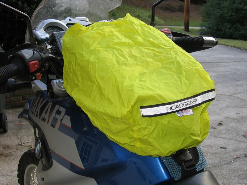 Hi-viz yellow rain cover is included. An elastic cord sewn around the bottom keeps it in place at highway speeds. It does keep the water out of the bag... trust me on this.