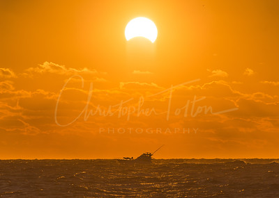 Eclipse over boat