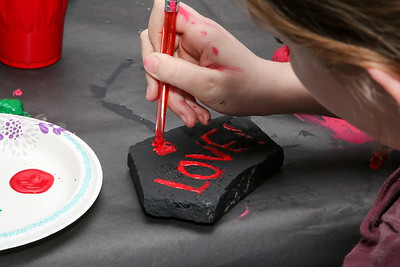 A two-sided Love/Hate design get painted on the pet rock.