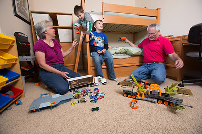 John and Debbie Button play with their grandchildren Anthony Ramirez, 5,lf, and Ezra Zion Dickey, 10, in a room they set up for their grandchildren in their Paso Robles home. The Buttons sold their million dollar home in Danville to buy one half the price on a bigger lot in Paso Robles, where they now own a chocolate shop. Their grandkids live three blocks away and are a big part of their lives. John who worked in high tech, is semi-retired, and likes to ride his motorcycles on the backroads of Paso Robles and up and down the coast. Debbie really likes working at the chocolate shop which they purchased after moving to Paso Robles.