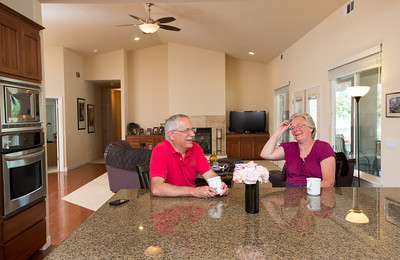 John and Debbie Button share a laugh over coffee in their Paso Robles home. The Buttons sold their million dollar home in Danville to buy one half the price on a bigger lot in Paso Robles, where they now own a chocolate shop. Their grandkids live three blocks away and are a big part of their lives. John who worked in high tech, is semi-retired, and likes to ride his motorcycles on the backroads of Paso Robles and up and down the coast. Debbie really likes working at the chocolate shop which they purchased after moving to Paso Robles.