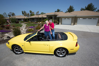 Their relationship started as high school sweathearts and now John and Debbie Button kiss in Debbie's yellow Mustang convertible in front of their Paso Robles home. The Buttons sold their million dollar home in Danville to buy one half the price on a bigger lot in Paso Robles, where they now own a chocolate shop. Their grandkids live three blocks away and are a big part of their lives. John who worked in high tech, is semi-retired, and likes to ride his motorcycles on the backroads of Paso Robles and up and down the coast. Debbie really likes working at the chocolate shop which they purchased after moving to Paso Robles.