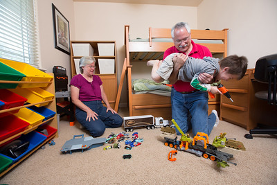 John and Debbie Button play with their grandchild Anthony Ramirez, 5, in a room they set up for their grandchildren in their Paso Robles home. The Buttons sold their million dollar home in Danville to buy one half the price on a bigger lot in Paso Robles, where they now own a chocolate shop. Their grandkids live three blocks away and are a big part of their lives. John who worked in high tech, is semi-retired, and likes to ride his motorcycles on the backroads of Paso Robles and up and down the coast. Debbie really likes working at the chocolate shop which they purchased after moving to Paso Robles.