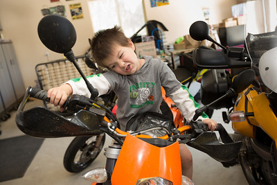 Anthony Ramirez, 5, plays on one of his grandfather's motorcycles in the Button's garage in Paso Robles. John and Debbie Button sold their million dollar home in Danville to buy one half the price on a bigger lot in Paso Robles, where they now own a chocolate shop. Their grandkids live three blocks away and are a big part of their lives. John who worked in high tech, is semi-retired, and likes to ride his motorcycles on the backroads of Paso Robles and up and down the coast. Debbie really likes working at the chocolate shop which they purchased after moving to Paso Robles.