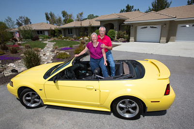 John and Debbie Button stand in Debbie's yellow Mustang convertible in front of their Paso Robles home. The Buttons sold their million dollar home in Danville to buy one half the price on a bigger lot in Paso Robles, where they now own a chocolate shop. Their grandkids live three blocks away and are a big part of their lives. John who worked in high tech, is semi-retired, and likes to ride his motorcycles on the backroads of Paso Robles and up and down the coast. Debbie really likes working at the chocolate shop which they purchased after moving to Paso Robles.