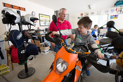 John Button watches his grandson Anthony Ramirez, 5, sit on one of his motorcycles in Button's garage in Paso Robles. Button is an avid rider and chose his residence partly because of the location in which to ride his motorcycles. Button and his wife Debbie sold their million dollar home in Danville to buy one half the price on a bigger lot in Paso Robles, where they now own a chocolate shop. Their grandkids live three blocks away and are a big part of their lives. John who worked in high tech, is semi-retired, and likes to ride his motorcycles on the backroads of Paso Robles and up and down the coast. Debbie really likes working at the chocolate shop which they purchased after moving to Paso Robles.