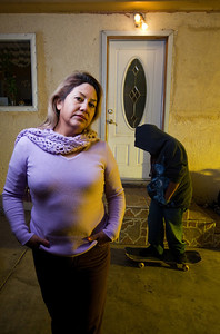 Teresa Arredondo,lf, stands with her son, Roberto,11, who rides a skateboard at their Bakersfield home on Mon. November 7th, 2011.
