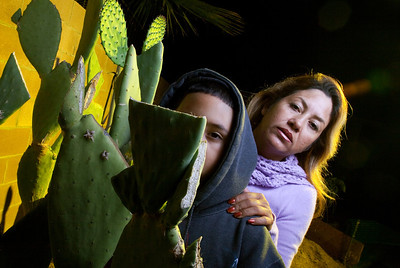 Teresa Arredondo,rt, stands with her son, Roberto,11, in their backyard behind a cactus plant at their Bakersfield home on Mon. November 7th, 2011.