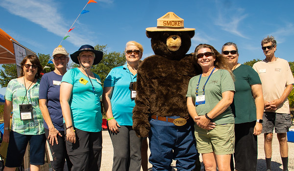 Smokey the Bear posing with Elm Fork Chapter Texas Master Naturalists at the Grand Opening of the Nature Center at Johnson Branch State Park.