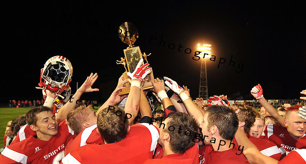 The St Ansgar Saints hold the L.R. Falk Traveling Trophy high after shutting out Osage 44-0 on Friday, September 6, 2014 in St Ansgar, Iowa. (EJ Photo/ Steve Pope)