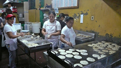 Lady on the left is molding the pupusas, one by one...