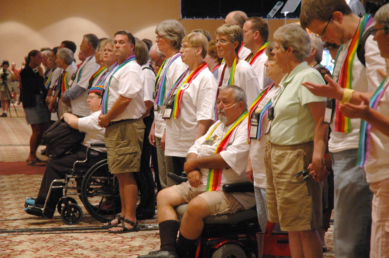 Visitors to the Churchwide Assembly (along with some Voting Members) stand in the Voting Members section of the plenary hall.