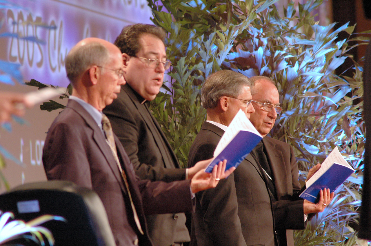 Heber Rast (President, Lutheran Men in Mission) The Rev. Randall R. Lee (Director, Department for Ecumenical Affairs) President Kieshnick (LC – MS) and Bp. Blaire (Roman Catholic) sing from the ELCA Churchwide Assembly's song book.