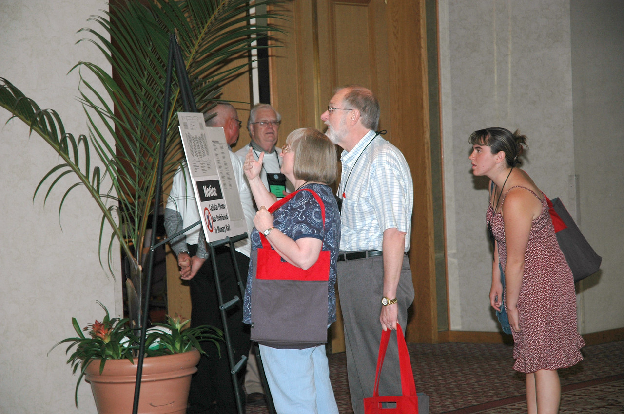 Voting members, visitors, and guests look for their seats on the plenary hall plan.
