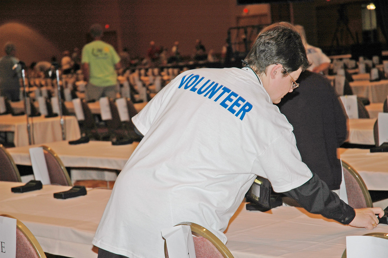A volunteer sets the table in the plenary hall.
