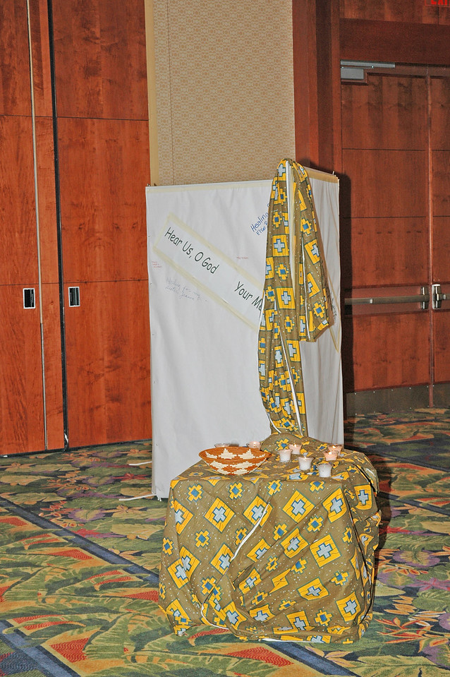 A prayer petition screen, candles, cloth, and a basket grace a table in the prayer chapel - part of the worship space