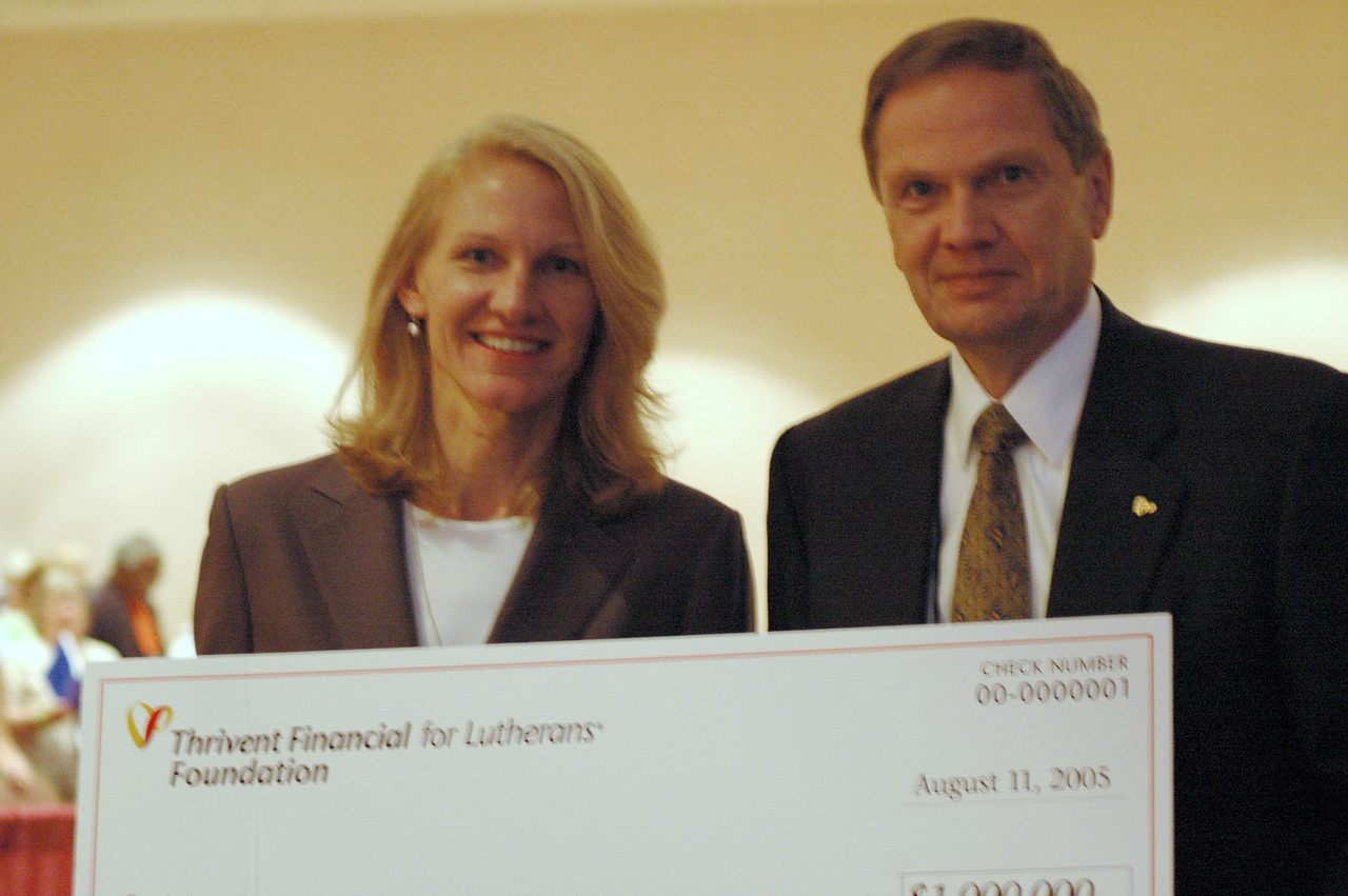 Cindy Halverson (Director, ELCA Fund for Leaders in Mission) and John Gilbert hold a $1 million check from Thrivent.