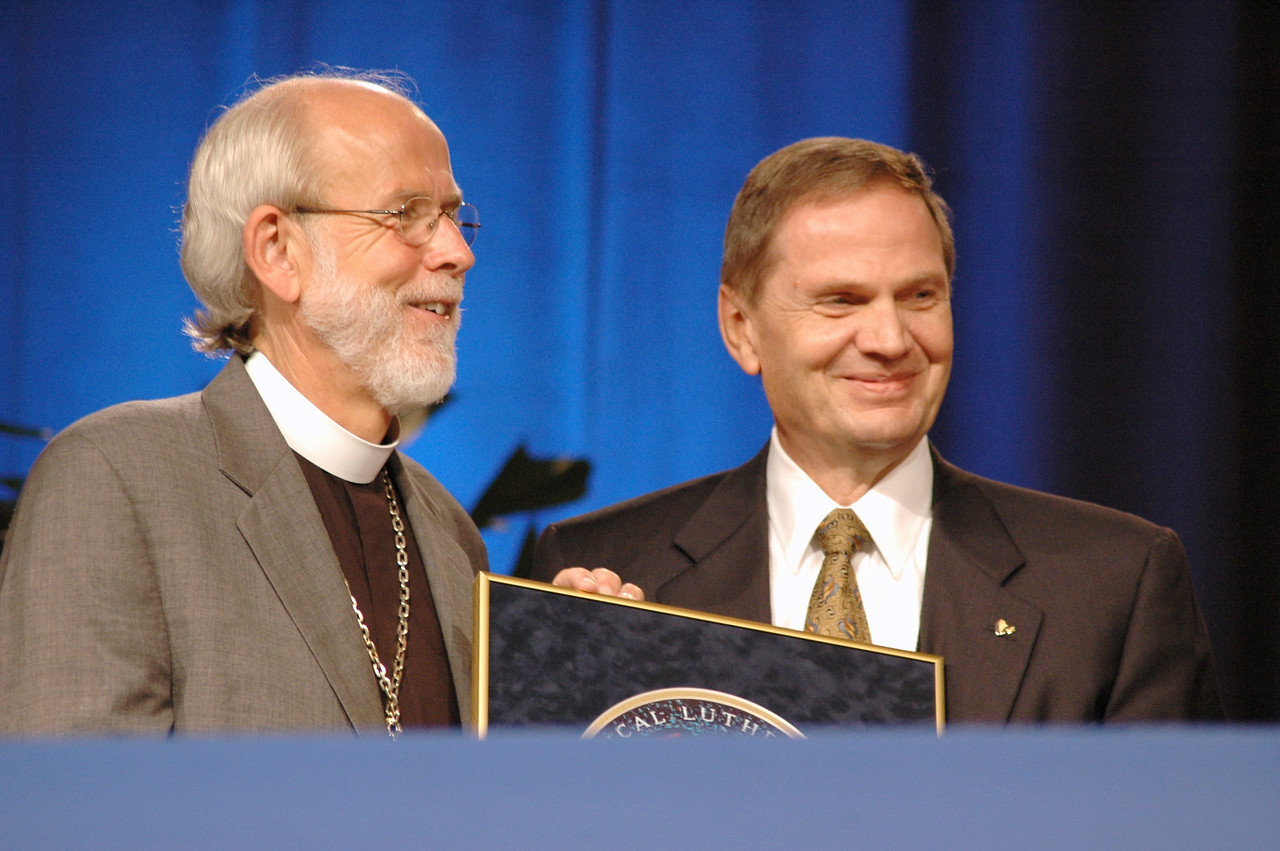 Bp. Hanson honors John Gilbert with a mosaic of the ELCA emblem.  It is inscribed with the verses from 1 Cor. 12:4-7.