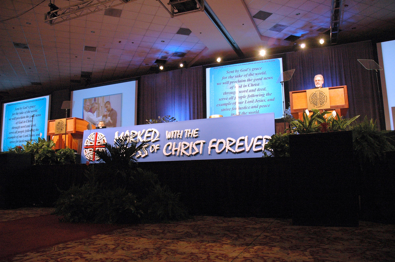 Large screens in the plenary hall help participants understand Pr. Charles Miller's presentation on the ELCA churchwide organization's restructuring.