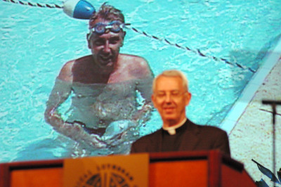 """""""We are one church,"""" Secretary Almen reminded. With a video clip from his 1991 report behind him, Almen related again how, just as with swimming, many parts do make one cohesive whole."""