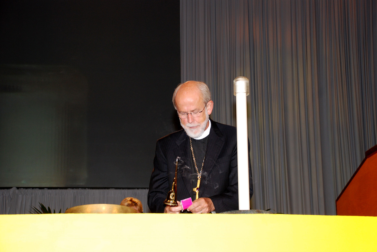 Bishop Hanson re-lighting the candle for during opening prayer at the Plenary 8 session.