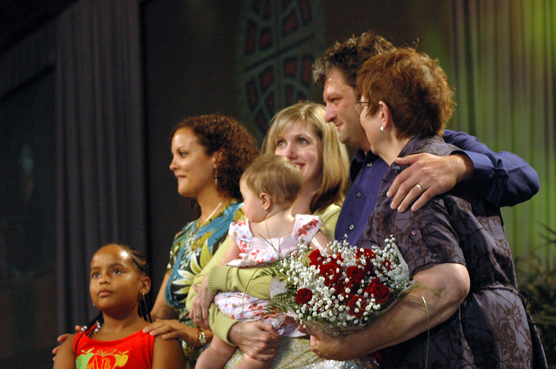 Lowell Almen's family stands on stage as Lowell Almen receives the Servus Dei medal presentation.